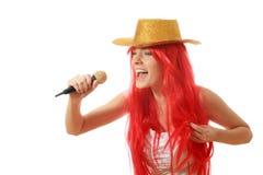La mujer joven con los accesorios leídos del pelo y del oro canta en alta voz en un micrófono Fotografía de archivo libre de regalías