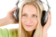 La mujer joven con los auriculares escucha la música Fotos de archivo libres de regalías