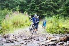 La mujer joven con los niños en las bicis vadea la corriente Imagen de archivo