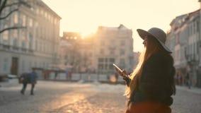 La mujer joven con los ojos azules hermosos en un sombrero gris y un pelo largo entra en la ciudad comunica vía smartphone almacen de video