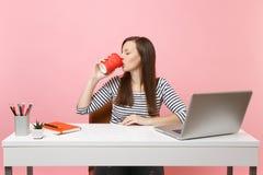 La mujer joven con los ojos cerrados bebe el café o el té de la taza para gozar el trabajar en el proyecto que se sienta en la of fotografía de archivo libre de regalías