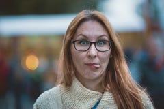 La mujer joven con los vidrios y los labios rojos muestra la lengua, al aire libre Imágenes de archivo libres de regalías