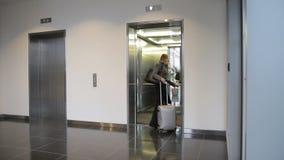 La mujer joven con la maleta camina en el elevador interior almacen de metraje de vídeo