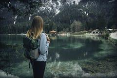 La mujer joven con la mochila se está colocando en la costa del lago foto de archivo