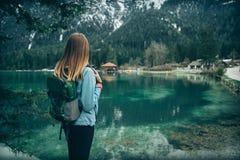 La mujer joven con la mochila se está colocando en el lago foto de archivo