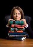 La mujer joven con muchos reserva en el escritorio imágenes de archivo libres de regalías