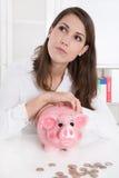La mujer joven con sus ahorros está soñando con su día de fiesta próximo Imagenes de archivo
