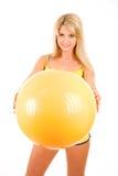 La mujer joven con una bola entra para la aptitud Imagen de archivo libre de regalías