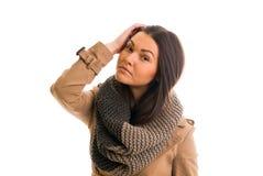 La mujer joven con una bufanda gris está mirando todo derecho Imagen de archivo