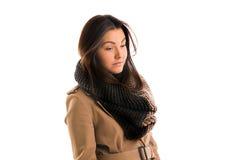 La mujer joven con una bufanda gris está mirando todo derecho Foto de archivo