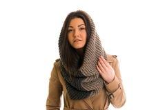 La mujer joven con una bufanda gris está mirando todo derecho Fotografía de archivo