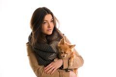 La mujer joven con una bufanda gris y un pequeño perro está mirando derecho Imagen de archivo libre de regalías