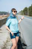 La mujer joven con una maleta está haciendo autostop en el camino Imagen de archivo