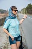 La mujer joven con una maleta está haciendo autostop en el camino Fotografía de archivo