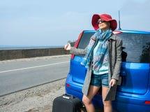 La mujer joven con una maleta está haciendo autostop en el camino cerca del mar Fotografía de archivo libre de regalías