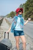 La mujer joven con una maleta está haciendo autostop en el camino cerca del mar Fotos de archivo