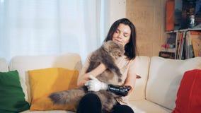 La mujer joven con una mano biónica está jugando con su gato