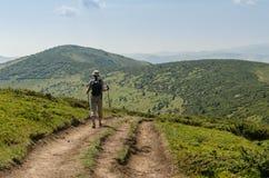 La mujer joven con una mochila que camina cuesta arriba para enarbolar de la montaña imagen de archivo libre de regalías