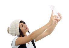 La mujer joven con una tableta hace un selfie, en blanco Fotos de archivo