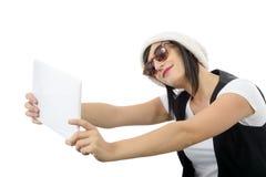 La mujer joven con una tableta hace un selfie, en blanco Fotos de archivo libres de regalías