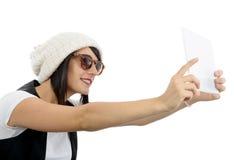 La mujer joven con una tableta hace un selfie, en blanco Imagenes de archivo
