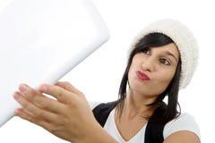 La mujer joven con una tableta hace un selfie, en blanco Imagen de archivo libre de regalías