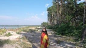La mujer joven con una tela escocesa camina en la playa cerca del bosque almacen de video