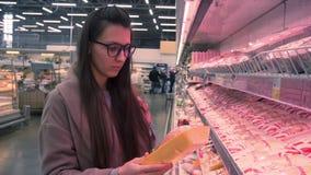 La mujer joven con vidrios y una capa en un supermercado elige los paquetes de carne del pollo