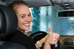 La mujer joven conduce el coche en la estación del lavado