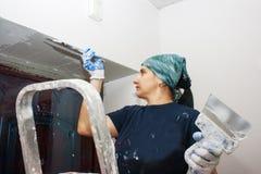 La mujer joven consigue la pared blanca del yeso Fotografía de archivo libre de regalías