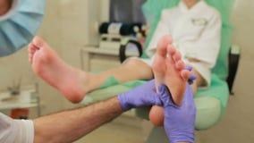 La mujer joven consigue un masaje del pie en el salón del balneario almacen de video