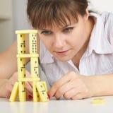 La mujer joven construye exactamente la torre de dominós fotografía de archivo