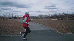 La mujer joven corre en parque en d?a nublado metrajes