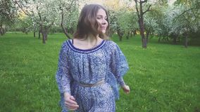 La mujer joven corre en un manzanar en las flores de la primavera blancas Retrato de una muchacha hermosa en la fruta de la tarde almacen de metraje de vídeo