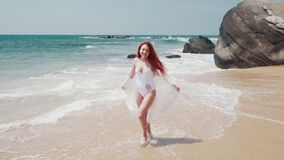 La mujer joven corre a lo largo de la playa del océano en un día soleado almacen de video