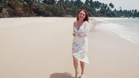 La mujer joven corre a lo largo de la playa del océano en un día soleado