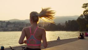 La mujer joven corre por la mañana, el sol está subiendo brillantemente, gente se está sentando por la orilla Cámara lenta almacen de video
