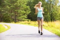 La mujer joven corre solamente al aire libre en el bosque Imagen de archivo