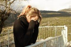 La mujer joven cubre ojos con sus manos Fotografía de archivo libre de regalías
