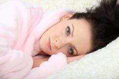 La mujer joven cuidadosa miente relajándose y descansando con su cabeza en las manos Imagen de archivo