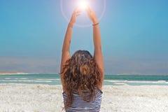 La mujer joven da la cogida de la energía del sol la muchacha de pelo largo se sienta en la orilla del mar muerto en Israel imagen de archivo