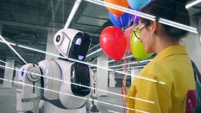 La mujer joven da el manojo de globos coloridos al androide metrajes