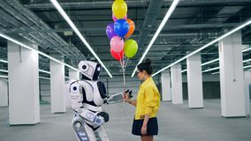 La mujer joven da muchos globos coloridos a su cyborg del amigo almacen de metraje de vídeo