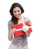 La mujer joven da un presente con el arqueamiento blanco Fotos de archivo libres de regalías