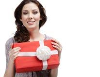 La mujer joven da un regalo con el arqueamiento blanco Imagenes de archivo
