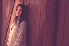 La mujer joven dappled en luz de la puerta de granero Imágenes de archivo libres de regalías