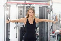 La mujer joven de la aptitud ejecuta ejercicio con la ejercicio-máquina fotografía de archivo