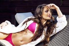 La mujer joven de la belleza después del balneario en bikini y el traje en el hotel recurren Foto de archivo libre de regalías