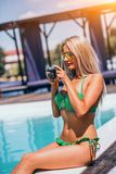 La mujer joven de Blondie en bikini verde se est? relajando cerca de piscina y de las fotos de observaci?n en la c?mara fotos de archivo