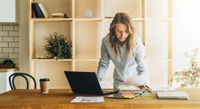 La mujer joven de la empresaria es tabla de cocina cercana derecha, documentos de la lectura, ordenador portátil de las aplicacio fotografía de archivo